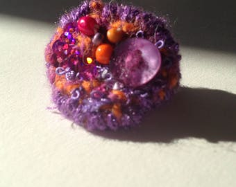Textile ring made of wool, ribbons, sequins, beads and buttons.