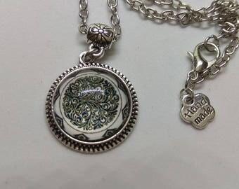 Black arabesques on white background glass cabochon necklace