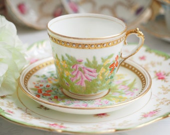 Antique Unmarked hand painted floral raised enamel cup and saucer