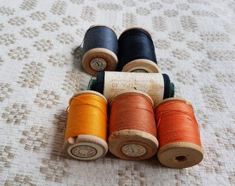 Set of six thick cotton black, yellow, brown, orange thread on wooden spools produced in the Soviet Union for sewing textile, crochet