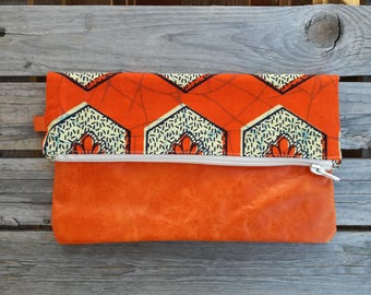 Clutch in orange leather and African fabric with orange background and yellow flowers