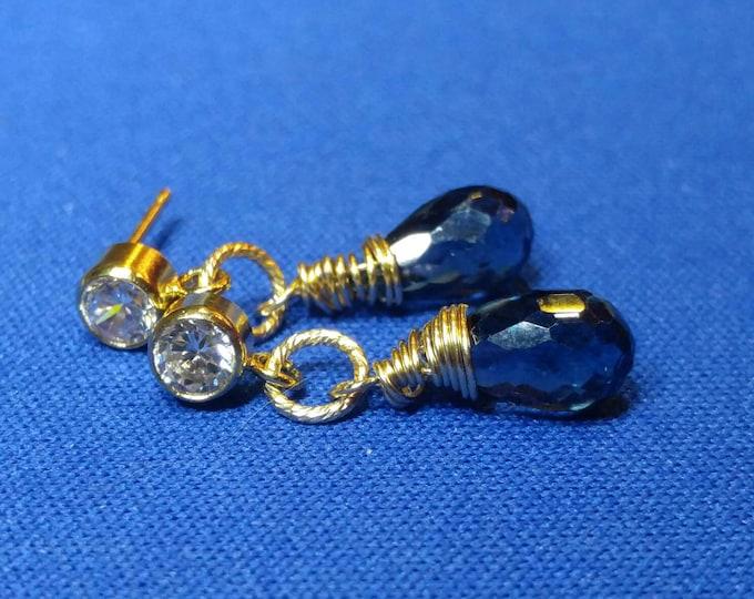 London blue Topaz earrings, post earrings with man made diamond studs. London blue briolets dangling from yellow gold stud post earrings.