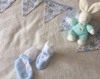 Knitted white socks and blue baby shoes