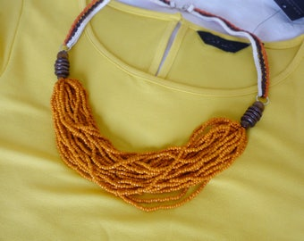 Necklace with strands of glass beads and braids worked