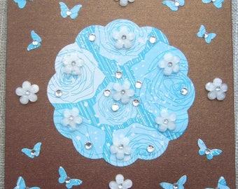 Greeting card made handmade iridescent golden brown background, embellishment, paper butterflies different shades of blue, flowers