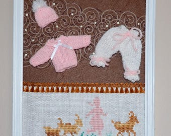 Pink and white miniature clothes setting on a brown background with embroidery cross stitch