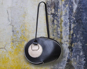 Handbag made of recycled bicycle inner shape of curved geometric black and white.