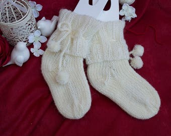 Handmade knitted socks for a little  girl, made of a lush cuff of mohair and rope, form cute pom-poms.