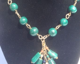 Traviata: Necklace of malachite, coral, lapis, mounted on gold rings.