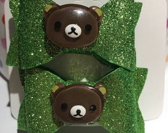 Beautiful foam bow with custom appliqué (glittery green with brown bear) on an alligator clip. (Set of 2).