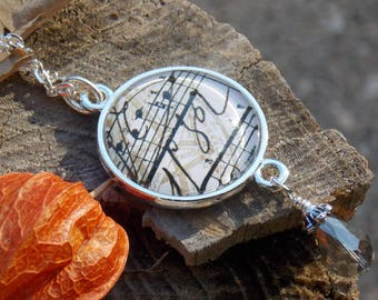 Decorative script music notes pendant necklace on a change in silvertone