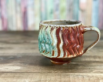Large soda fired mug. Stoneware with flashing slip and sprayed glazes, handmade cup, faceted with wiggle wire. Toasty warm soda glazed mug.