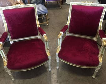 Pair of red velvet upholstered chairs with acanthus leaf details