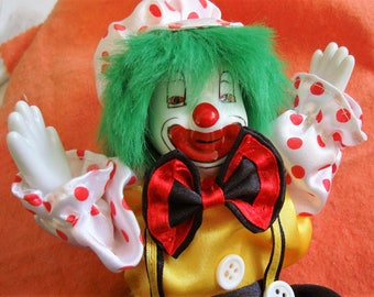 SATIN CLOTHED CLOWN is 8 1/2 inch tall.  his legs and arms move., his body is plastic, hair is wool.  Condition like new.