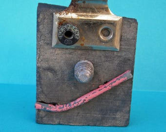 face art, mixed media, found items, recycled art, smile, mask, portrait, art on slate, robot, desk art, humorous, small face art, sculpture