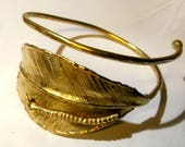Adjustable brass bracelet, with hammered leaf and worm that perforates it.
