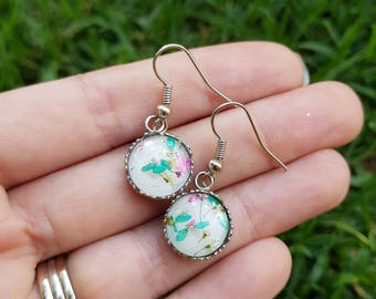 Real blue and pink flower and resin dangle drop earrings in a crown setting. Stainless surgical steel. Hypoallergenic. 1.2cm diameter