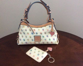 A Cute Authentic Dooney and Bourke Heart Multicolored Monogram with a Leather handle and a Coin Purse.
