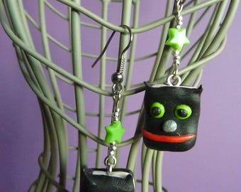 Platinum metal earrings with a black book owl made with polymer clay and green star bead
