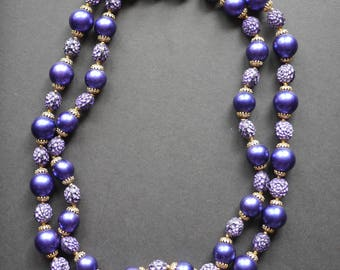 Purple double stranded beaded necklace with gold and purple carved beads