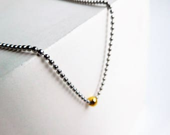 Minimalistic two toned necklace with a small golden bead
