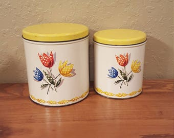 Set of 2 vintage Decoware nesting tin canisters with tulip design.  Vintage vibrant yellow and white retro kitchen canisters.