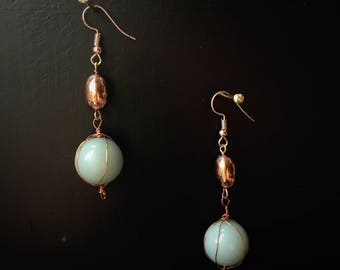 Bright, eye-catching rose-gold drop earrings with a soft pastel-green bead