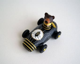 brown bear in a miniature bee car - black and yellow toy car