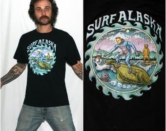 Surf Alaska Souvenir T Shirt. Funny Hipster Surfer T Shirt. Surfer And A Bear On A Fish T Shirt. Weird Alaska Surfing Art Shirt.