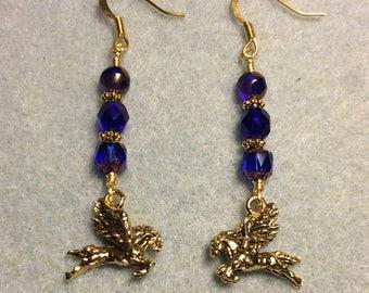 Gold Pegasus charm dangle earrings adorned with dark blue Czech glass beads.