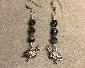 Silver guinea hen charm dangle earrings adorned with black Czech glass beads.