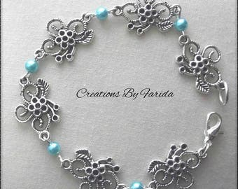 Bracelet curb chain with connector in the shape of flower and blue beads