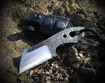 Small tactical knife with leather sheath.