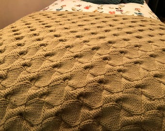 Handmade knit blanket with intricate weave in rich maple color