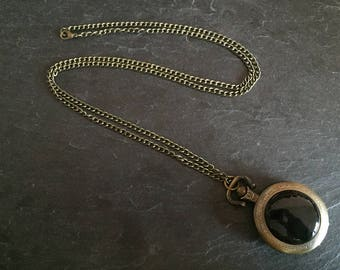 Necklace with onyx and a pocket watch.