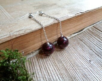 Earrings of a sphere on a chain with flowers of a wild rose inside.