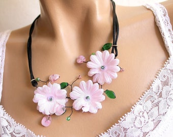 Necklace three pink flowers and green leaf beads.