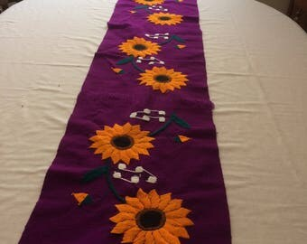 Table runner embroidered by hand .