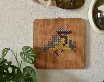 Handgemaakt geborduurd muurdecoratie - hout paneel met een pimpelmees. Vogeltje op takje voor je interieur