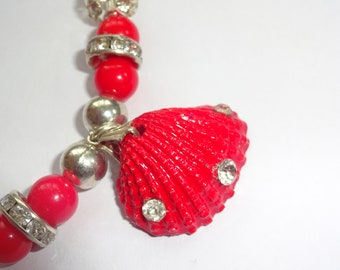 """new vibrant red real shell pendent. Decorated with rhinestones . strung up with red and silver beads .With a fancy back detail. 22"""" long."""