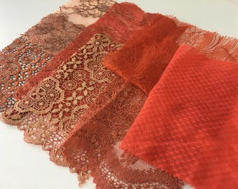 assortment of various smaller sheer lingerie tulle lace / mesh swatches — brick red /  burnt orange — different sizes and patterns