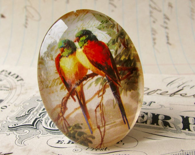 Pair of lovebirds perched on a branch, from our Beautiful Birds collection of handmade glass cabochons, 40x30mm oval cabochon, red, green