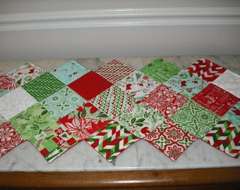 Christmas red, blue and green Table runner . 17 1/2 inches wide by 43 inches long.  Cotton. Polyester batting. Machine quilted.