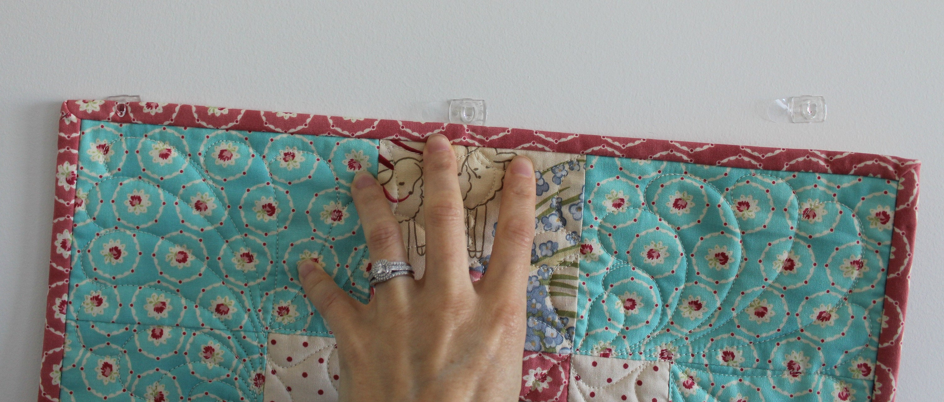 Slide the quilt into the hooks that are turned upside down and voila!  Your quilt is hanging!