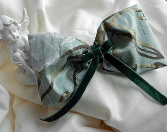 Silk green and gold hair bow placed on hair clip