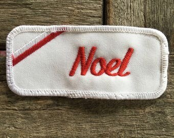 "Noel. A white work shirt name patch that says ""Noel"" in red script with white border"