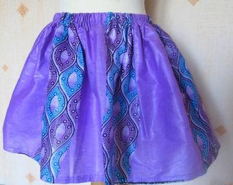 Girl in wax or purple African fabric skirt