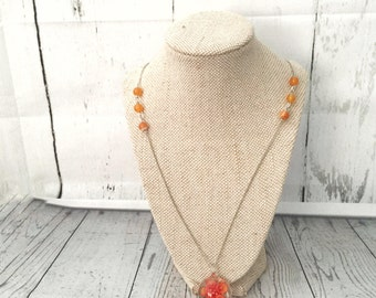 Chic sophisticated silver necklace with tangelo orange beads and flower charm.