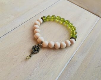 Beaded bracelet, peridot and unfished wooden beads with antique copper colored spacer beads and charm