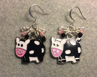 Black, pink, and white enamel cow charm earrings adorned with tiny dangling black, pink, and clear Czech glass beads.